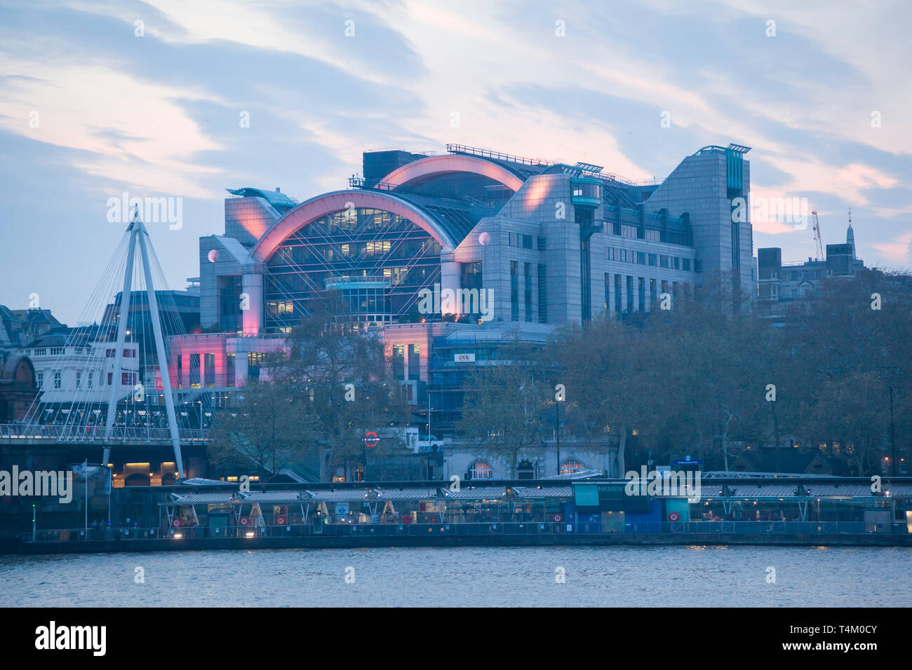 Charing Cross Station from the River Thames at dusk with pink floodlighting - Stock Image