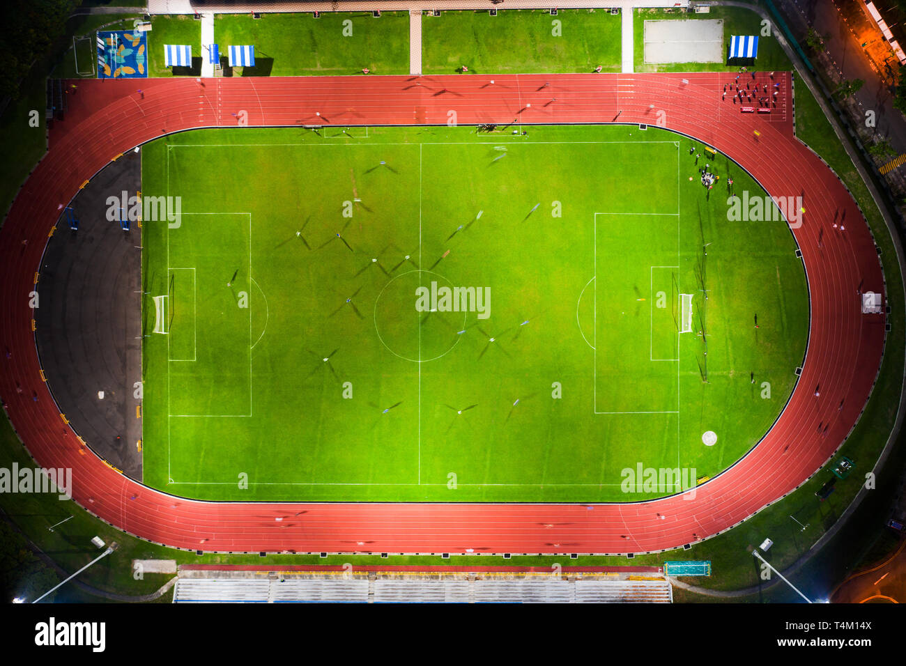 Aerial view of a soccer pitch with players playing soccer and a running track for joggers within a light up stadium. - Stock Image