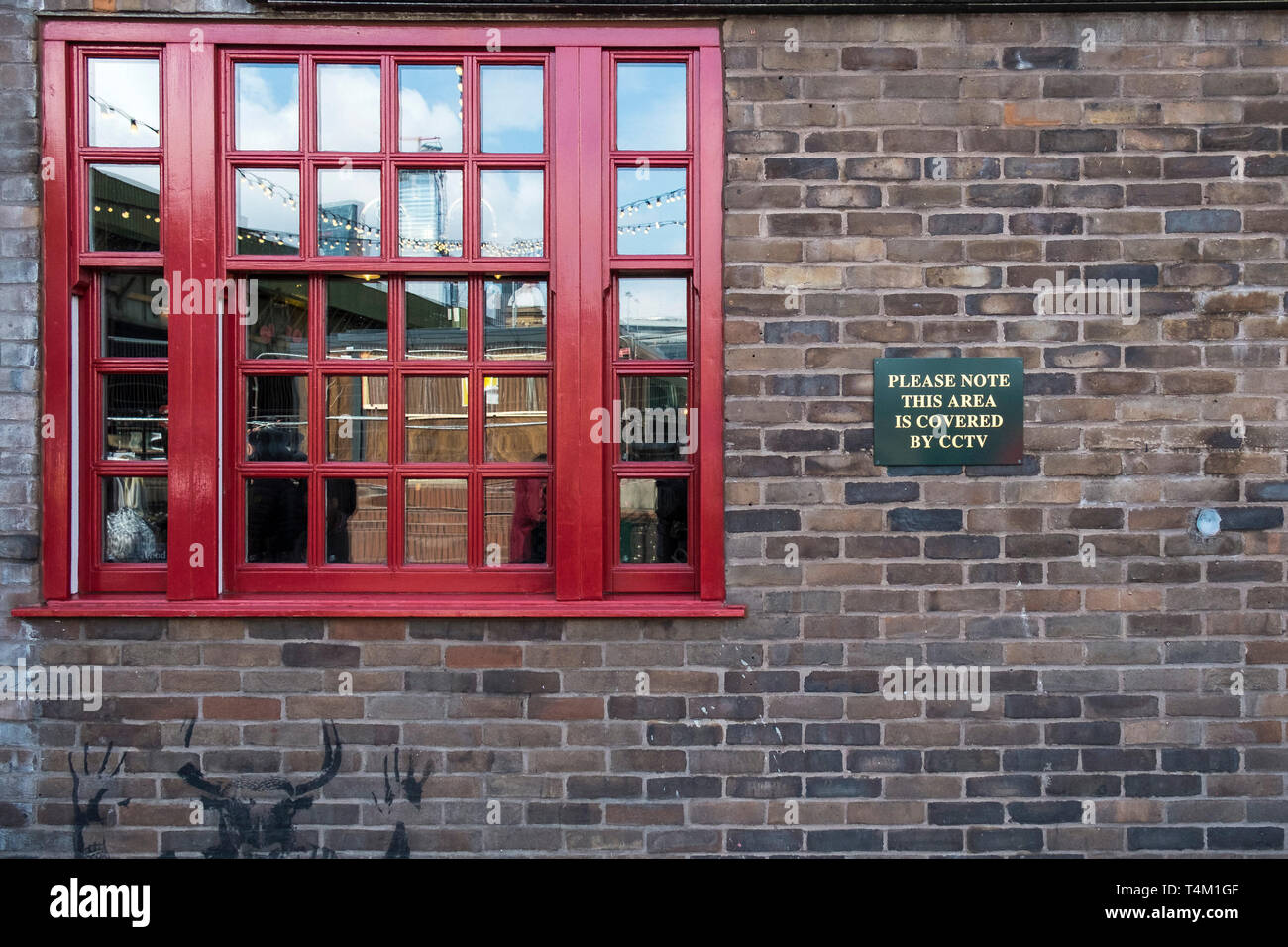 A red wooden sash window next to a sign warning CCTV coverage. - Stock Image