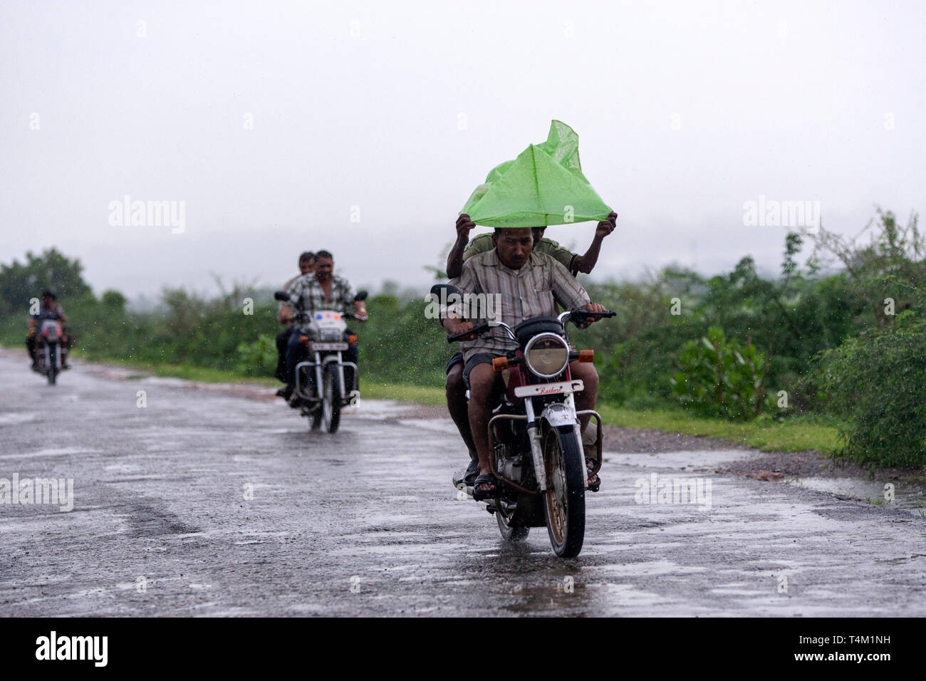 Bikers protecting with plastic bag the heavy rain in Rajasthan, India - Stock Image