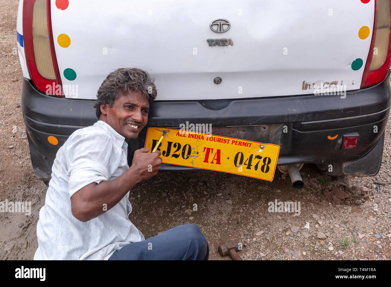 Man changing the car registration plate in Rajasthan, India - Stock Image