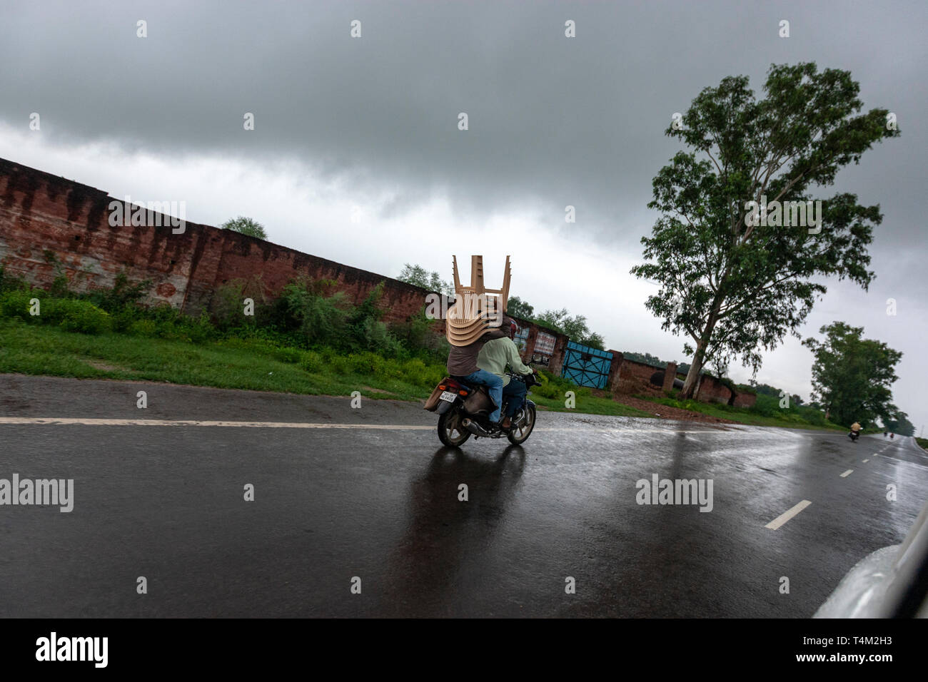 Motorbike with a passanger carrying plastic chairs under a heavy rain, Uttar Pradesh, India - Stock Image