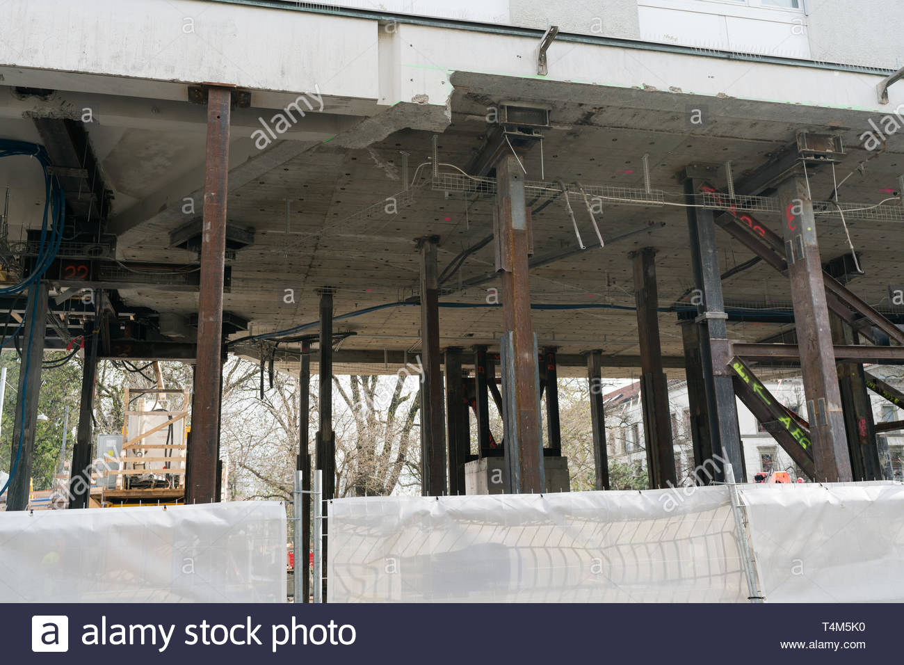 incredible view of how heavy industrial stilts hold up a multi-story building while the ground floor is demolished and rebuilt - Stock Image