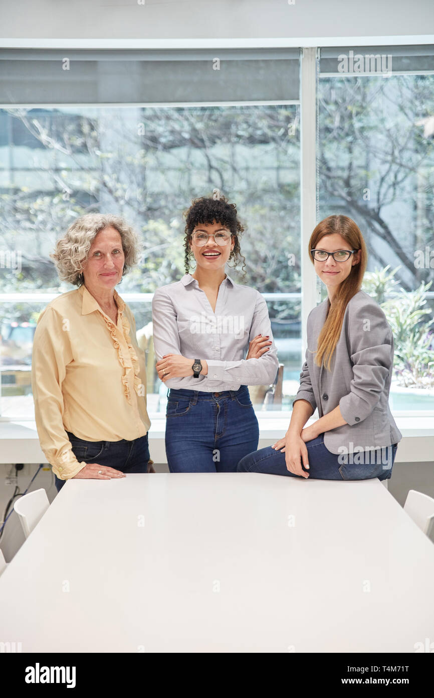 Three successful businesswomen in the office as a women quota concept - Stock Image