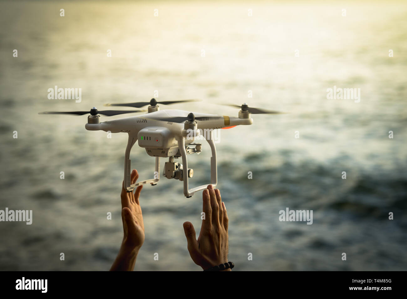 Drone flying on sea with human hands - Stock Image