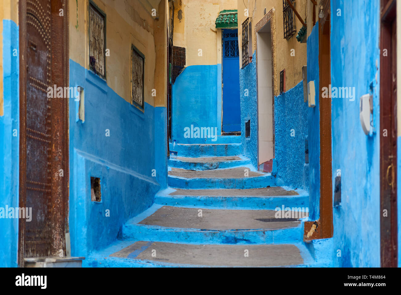 Typical blue painted alley with old door entrance in the medina of Tanger (Tangier), northern Morocco - Stock Image
