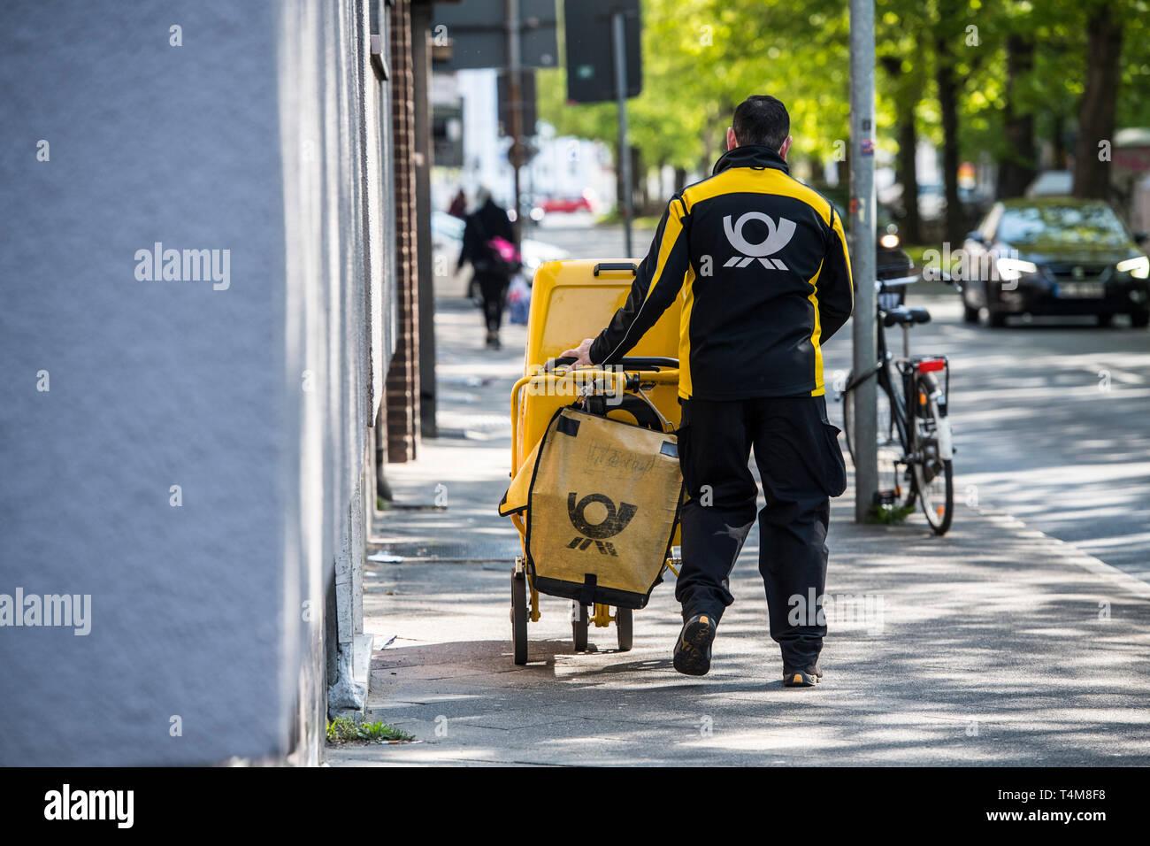 Postbote in der Großstadt zu Fuss unterwegs. - Stock Image