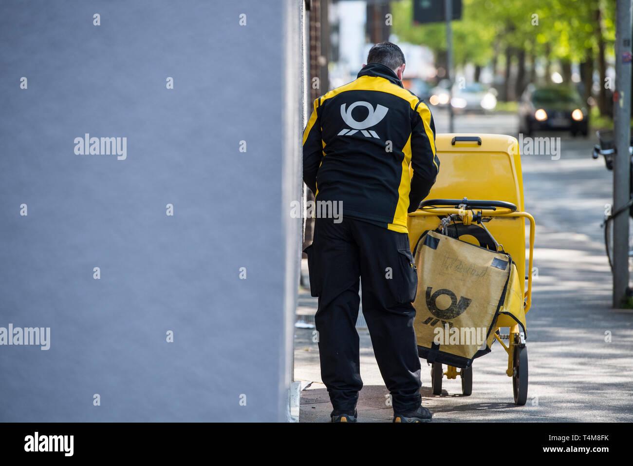 Postbote in der Großstadt zu Fuss unterwegs. Stock Photo