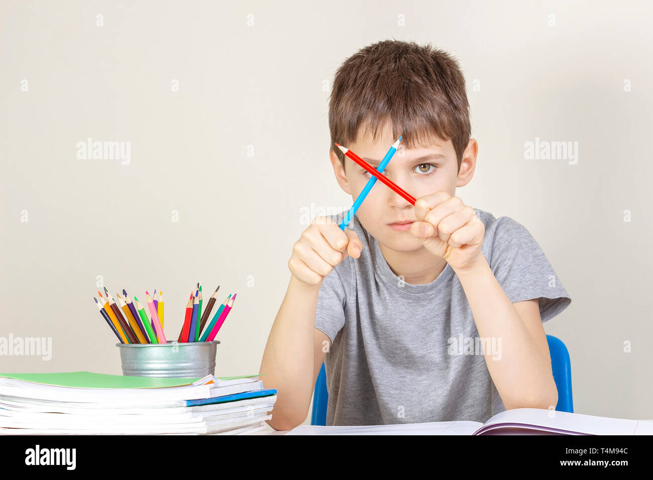 Sad angry boy have difficulties doing homework. - Stock Image
