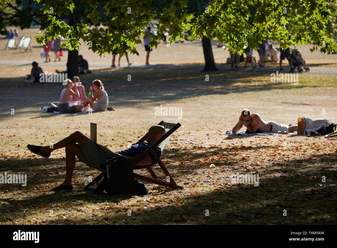 People relaxing in the sun, St James's Park, London, England, Great Britain Stock Photo