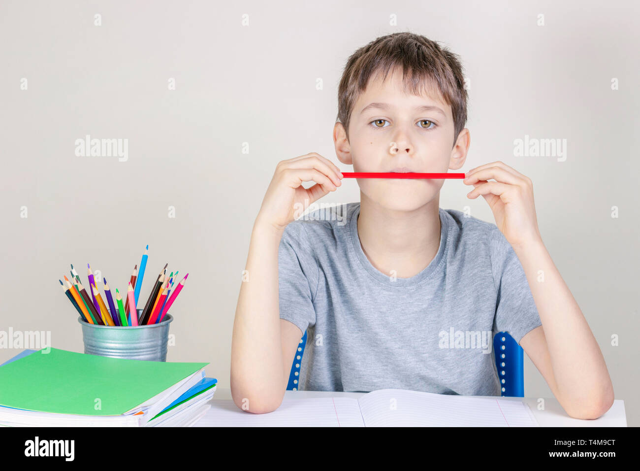 Kid doing homework at the table and thinking or dreaming - Stock Image