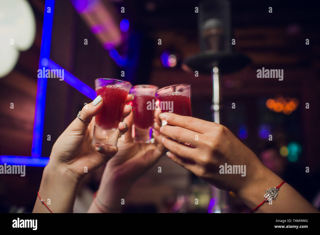Cropped image of hands having shots against flying colours. - Stock Image