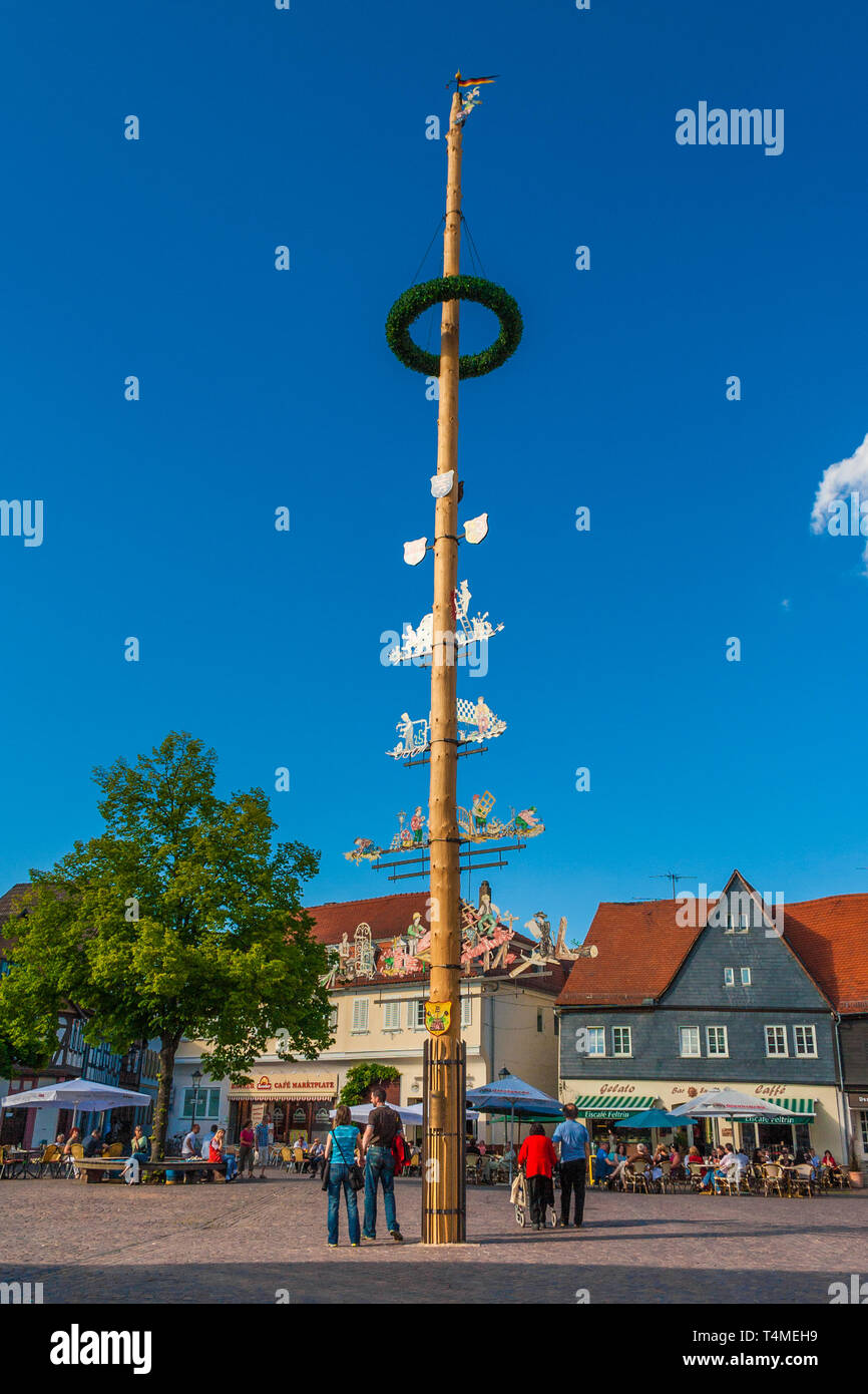 Full view of the maypole (Maibaum) standing on the marketplace in Seligenstadt, Germany on a nice sunny day with a blue sky. The decorated tree trunk... - Stock Image