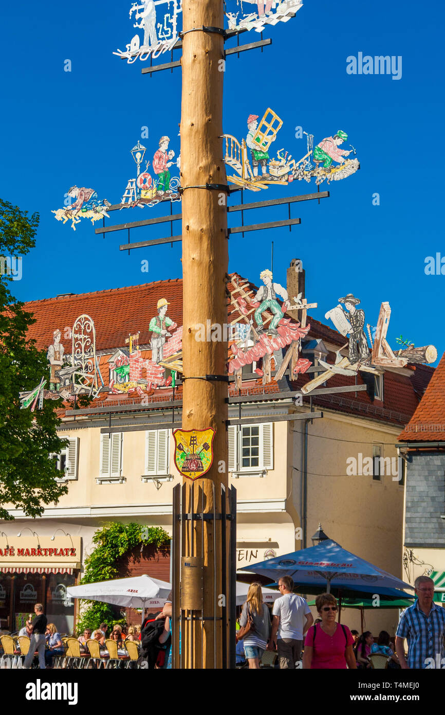 Great close-up view of a maypole or Maibaum, a tall wooden pole erected on the marketplace in Seligenstadt, Germany. The pole is decorated with... - Stock Image