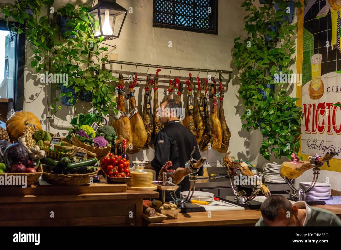 Malaga, Spain 04.04.2019: man waiter butcher in el pimpi restaurant in Malaga who cuts a slices of traditionally spanish jamon de bellota ham - Stock Image
