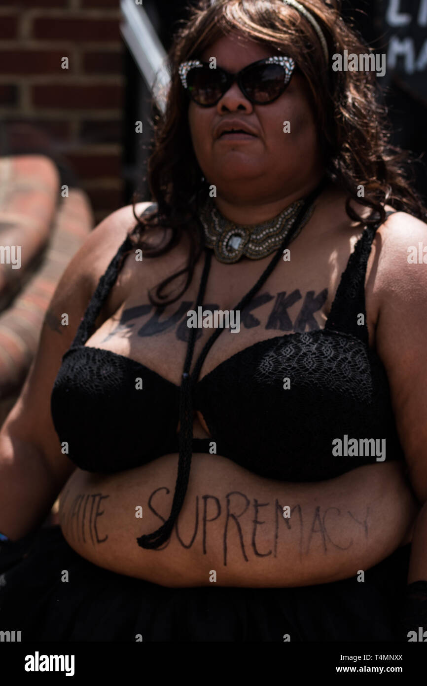 Black Woman in Sunglasses with Anti Racism Slogan on Front of Body Stock Photo