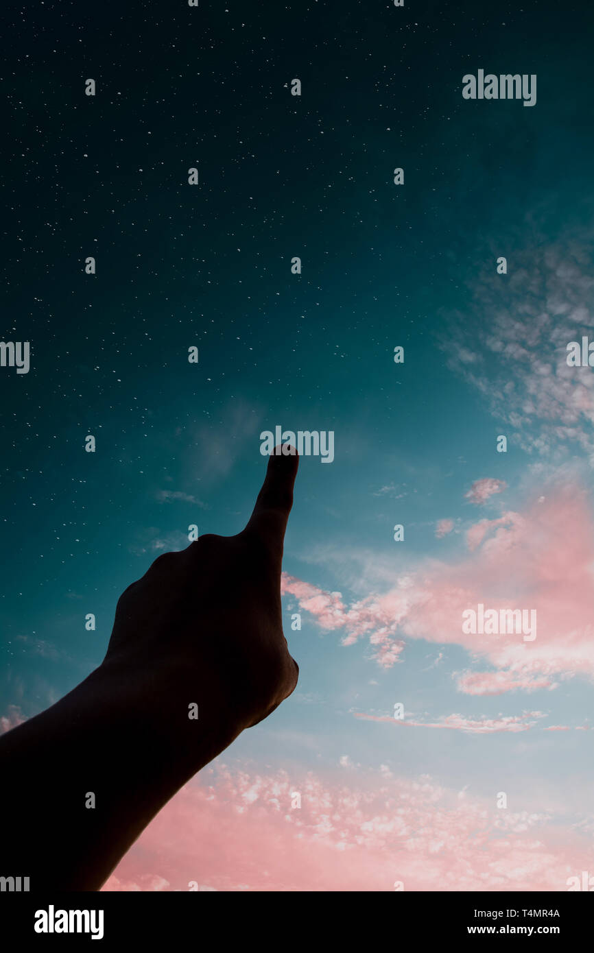 Hands silhouette pointing at the sky with stars during colorful sunset - Stock Image