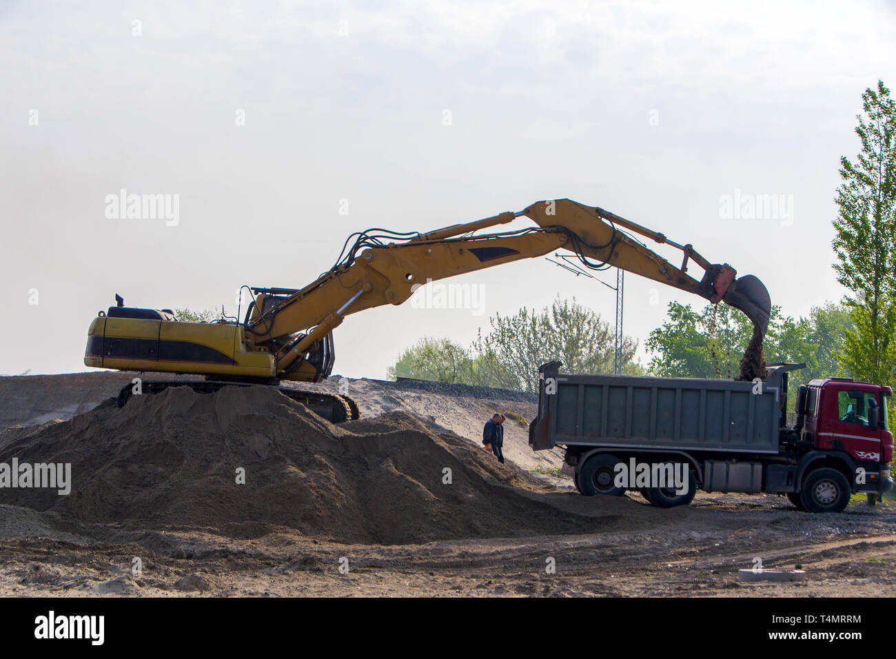Excavator loading sand in the truck on the construction of access roads for the bridge - Stock Image