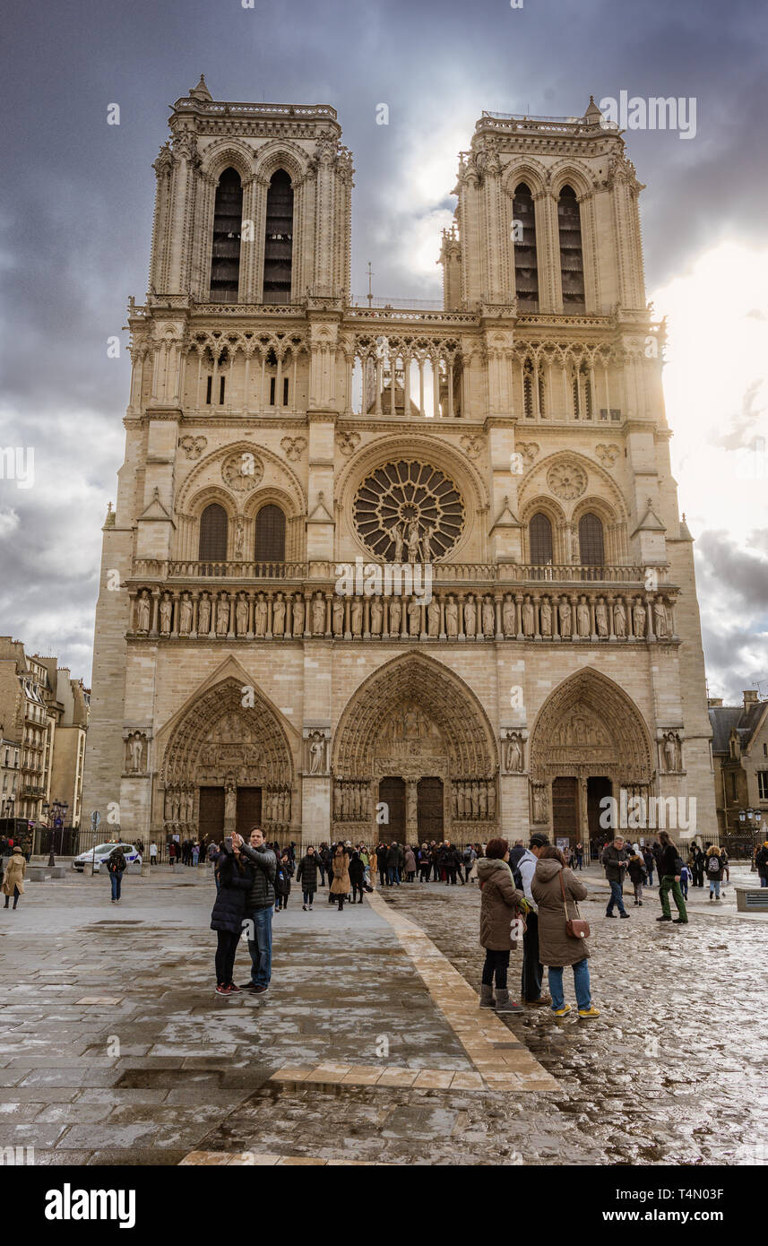 Tourists visiting the Cathedral Notre Dame de Paris - most famous Roman Catholic cathedral (1163 - 1345) on the eastern half of the Cite Island - Stock Image