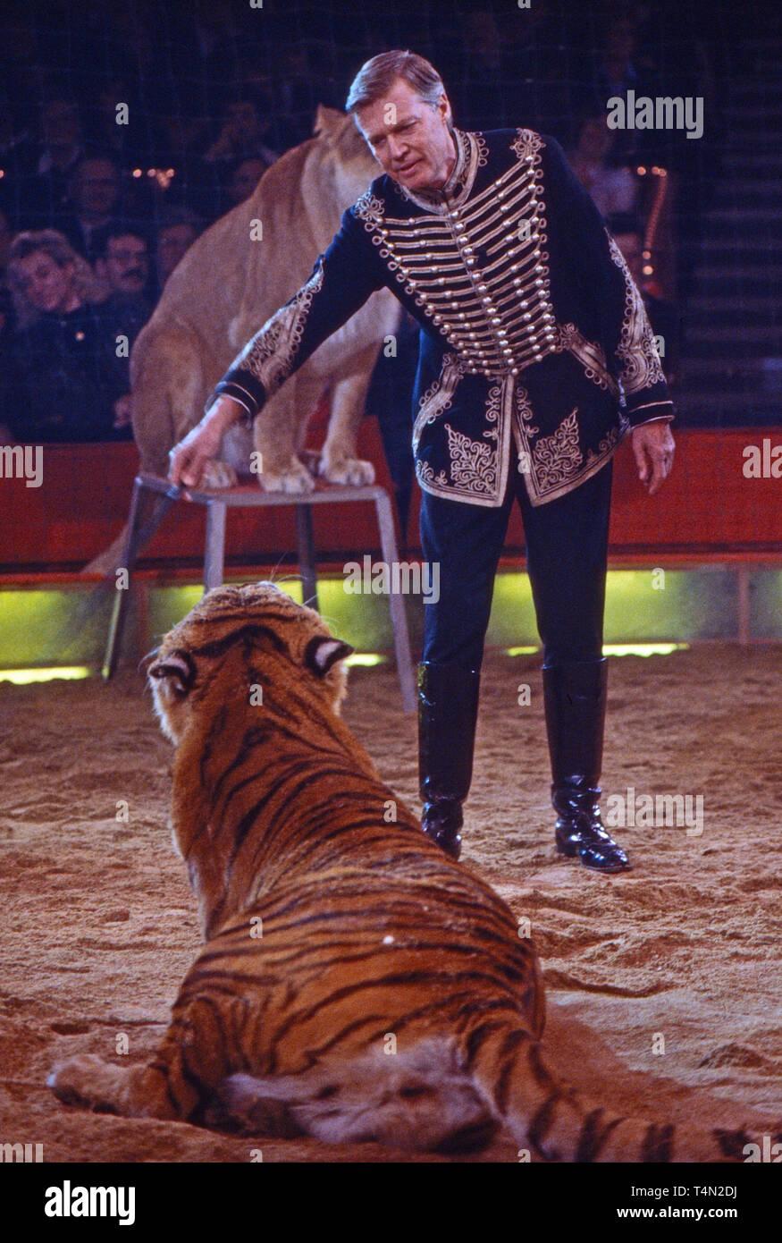 Karlheinz Böhm, österreichischer Schauspieler, bei der Tigerdressur in der Zirkussendung 'Stars in der Manege', Deutschland 1986. Austrian actor Karlheinz Boehm with tiger in a circus TV show, Germany 1986. - Stock Image