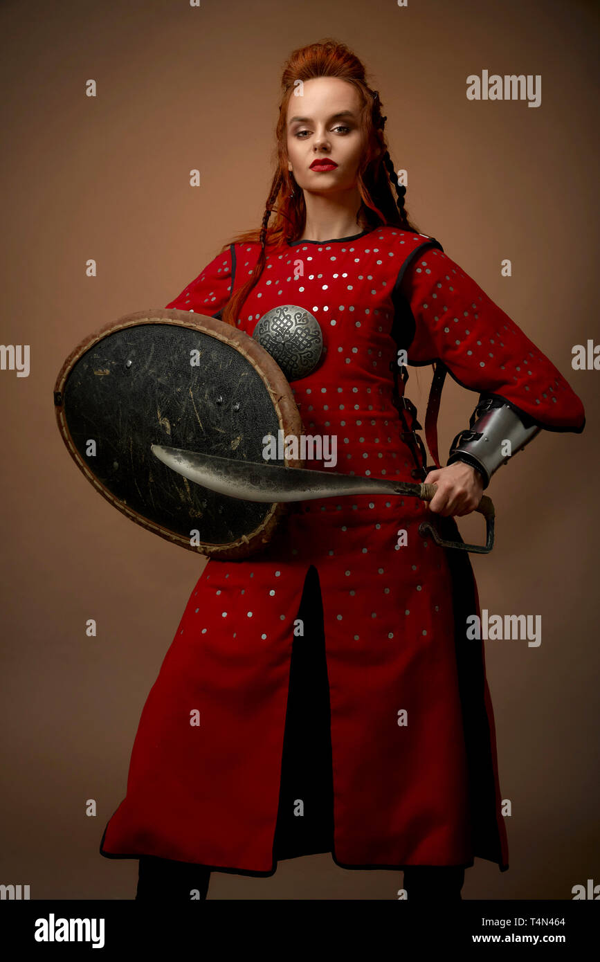 Brave, serious woman wearing as noble hero in red medieval tunic. Beautiful, charming model with ginger hair holding shield and dagger, posing in studio with weapon. - Stock Image