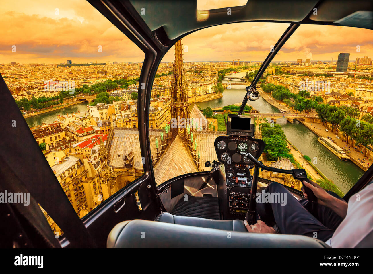 Helicopter cockpit flying at sunset on Notre Dame de Paris cathedral and on skyline of Paris, French capital, Europe. Scenic flight over Paris Stock Photo