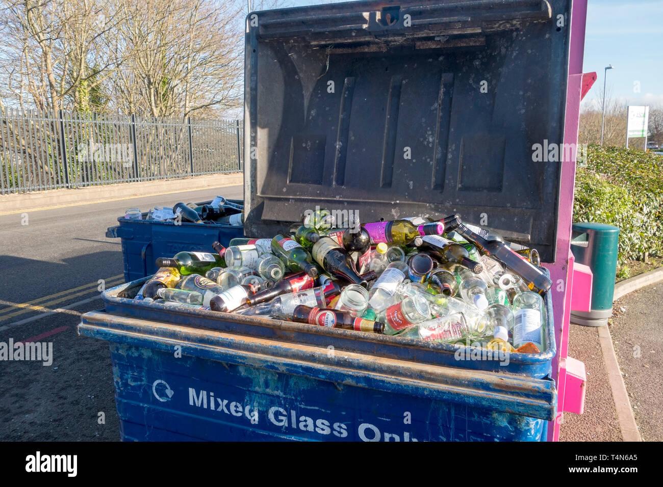 Full bottle mixed glass recycling bin - Stock Image