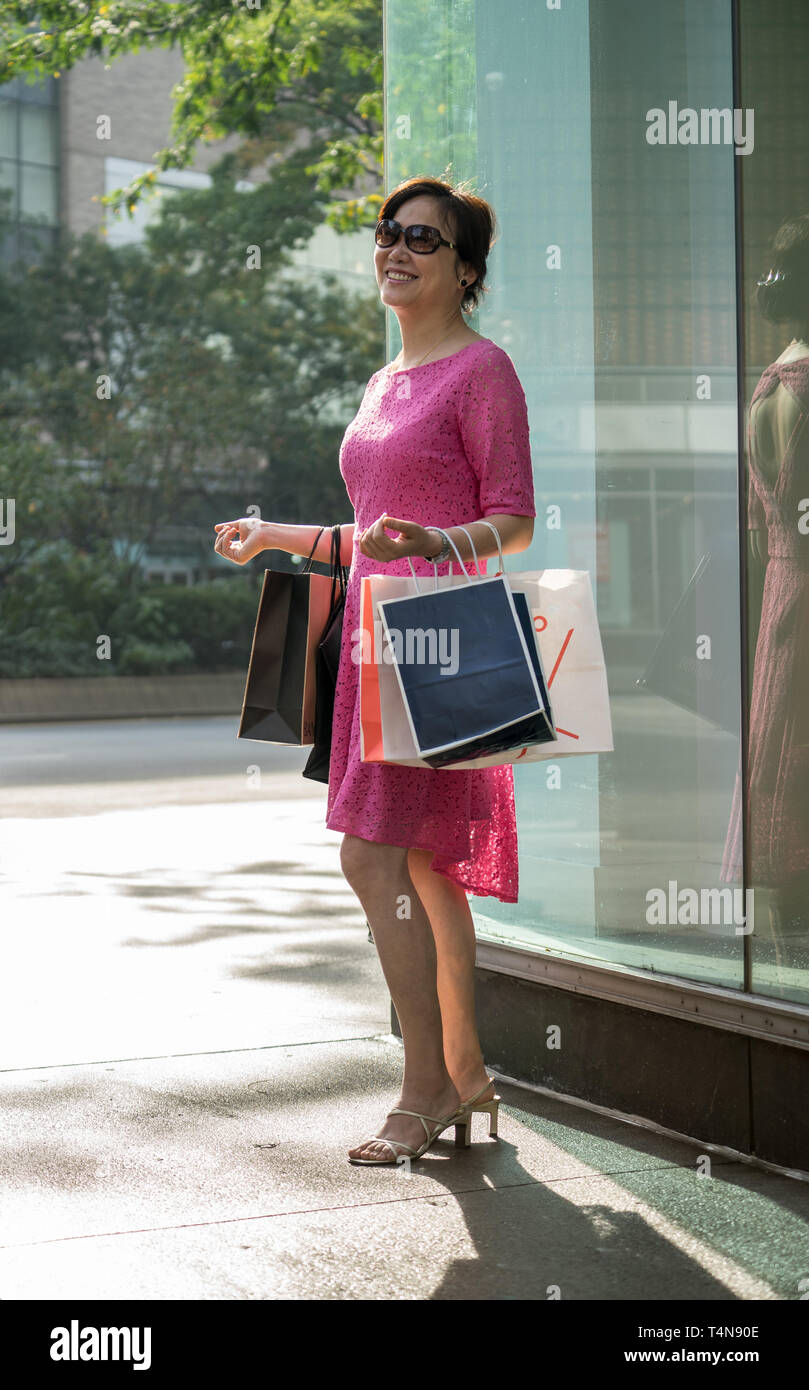 An asian woman shopping with many bags on hand. - Stock Image