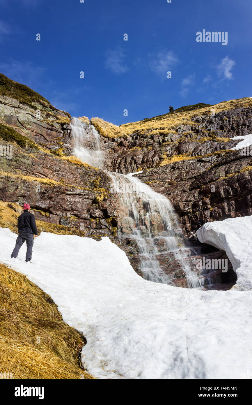 Mountain hiker with purple winter cap standing in front of the large, scenic, beautiful waterfall falling from red rocky cliff under the snow - Stock Image