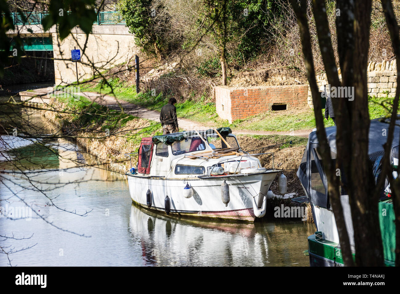 A man stood behind a small old and worn river cruiser boat moored on the Kennet and Avon canal in front of old world war 2 pill box. Stock Photo