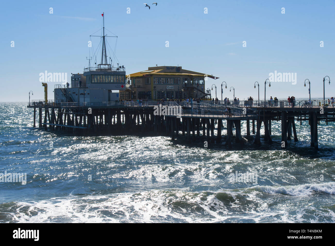 Tourists enjoying the world famous Santa Monica Pier during a high sea.  Exclusive - Stock Image