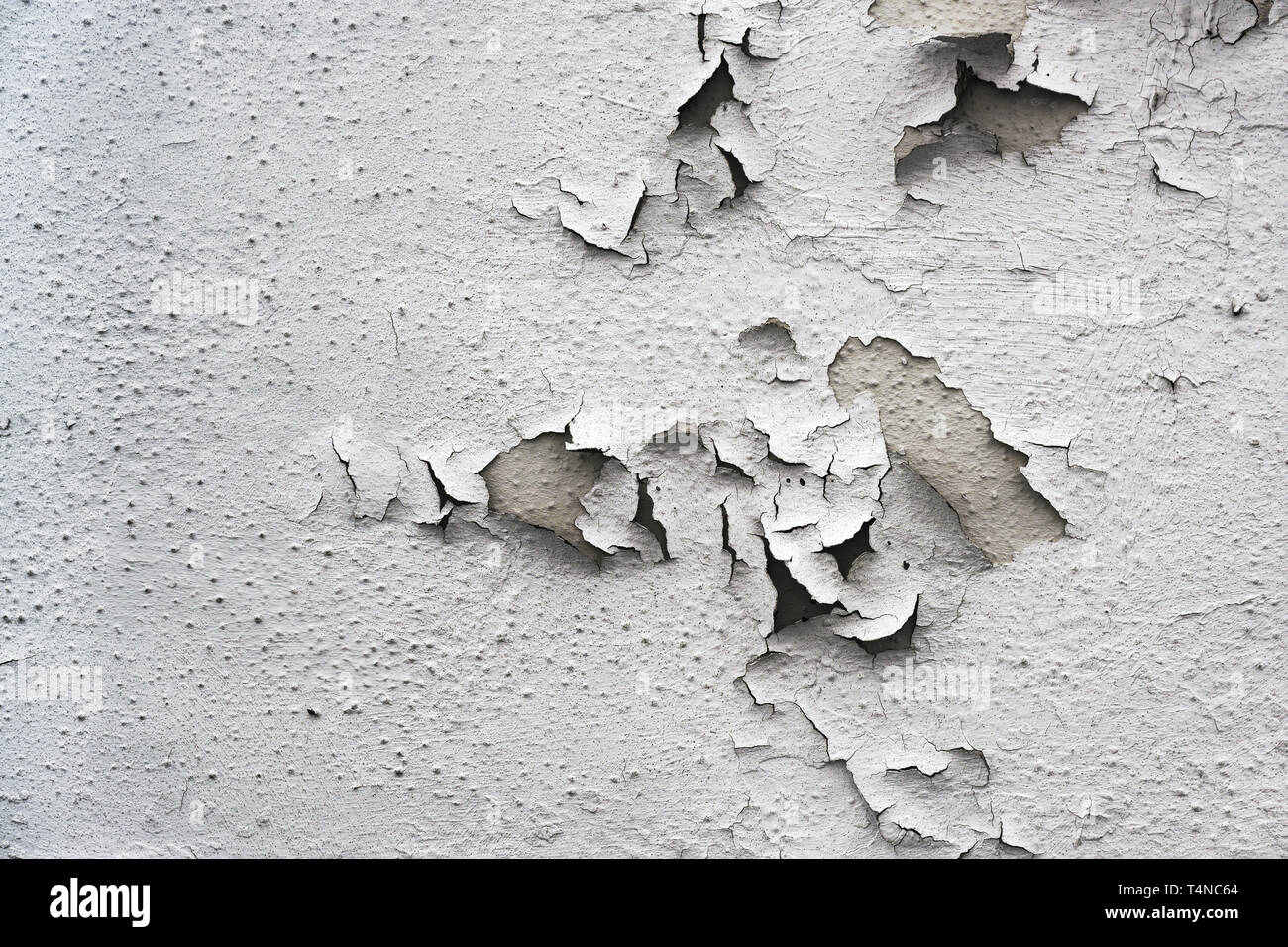 flaking gray paint on an old building, background texture for renovation concept, copy space Stock Photo