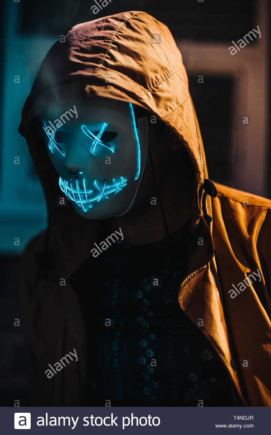 person wearing white illuminated mask and hoodie - Stock Image