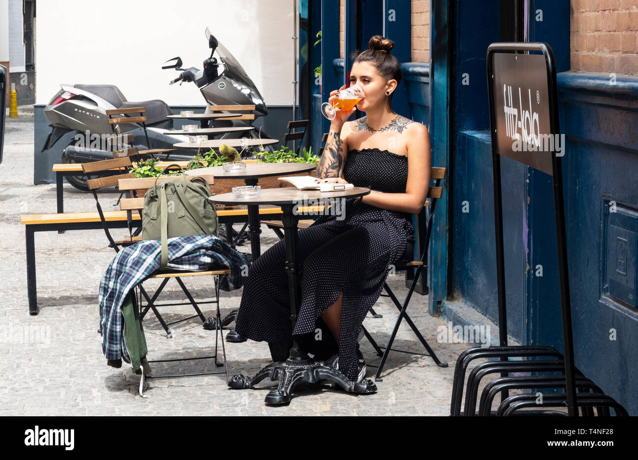 Young tattooed woman reading a paperback book and drinking beer at a cafe in Seville - Stock Image