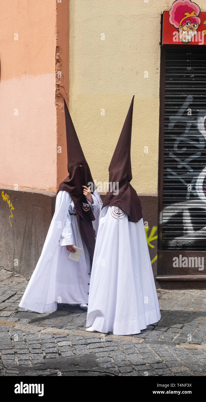 Young female Easter penitents in white robes and pointed brown hoods - Stock Image