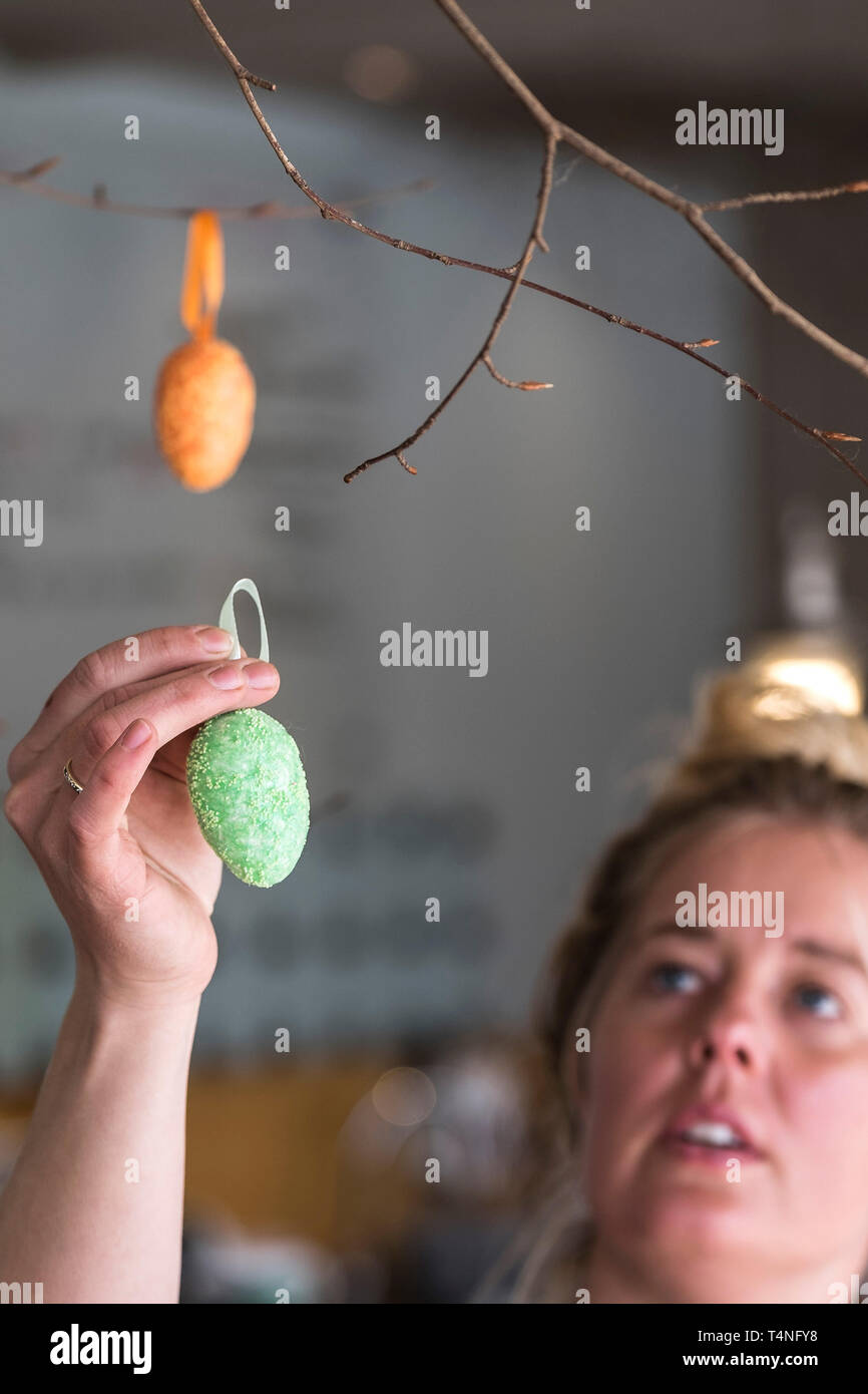 A woman carefully hanging an Easter egg decoration from a twig. - Stock Image