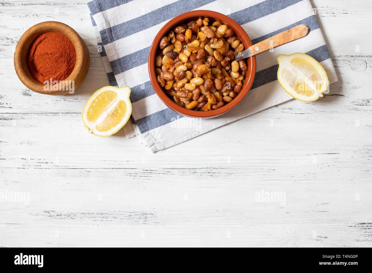 Prebranac. Balkan baked beans. Serbian, Montenegrin, Bosnian, Croatian, Slovenian cuisine. Uncooked beans, onion, lemon, paprika powder. White wooden Stock Photo