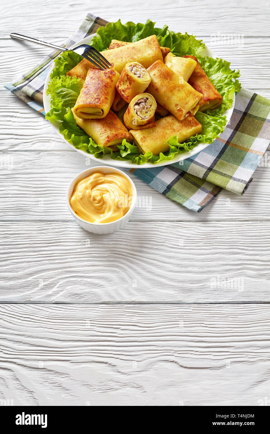 Savory crepe rolls with ground chicken meat and mushrooms filling served on a bad of fresh lettuce leaves on a white plate on a wooden table with chee - Stock Image
