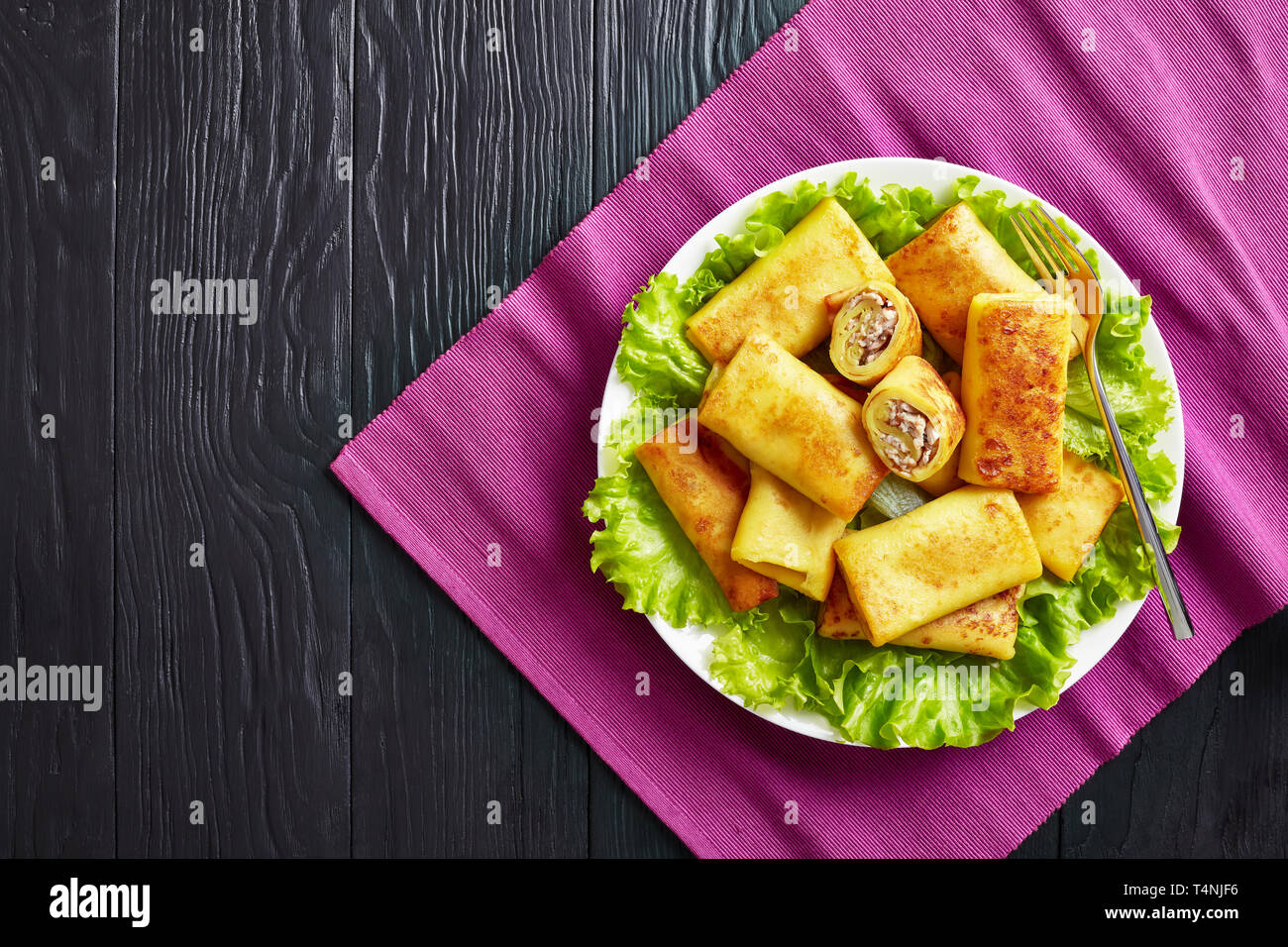 overhead view of Savory crepe rolls with ground chicken meat and champignon filling served on a bad of fresh lettuce leaves on a white plate on a blac - Stock Image