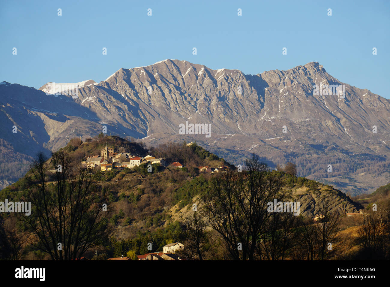 View of a small typical village on top of a hill in Southern France at sunset by the mountains - Stock Image