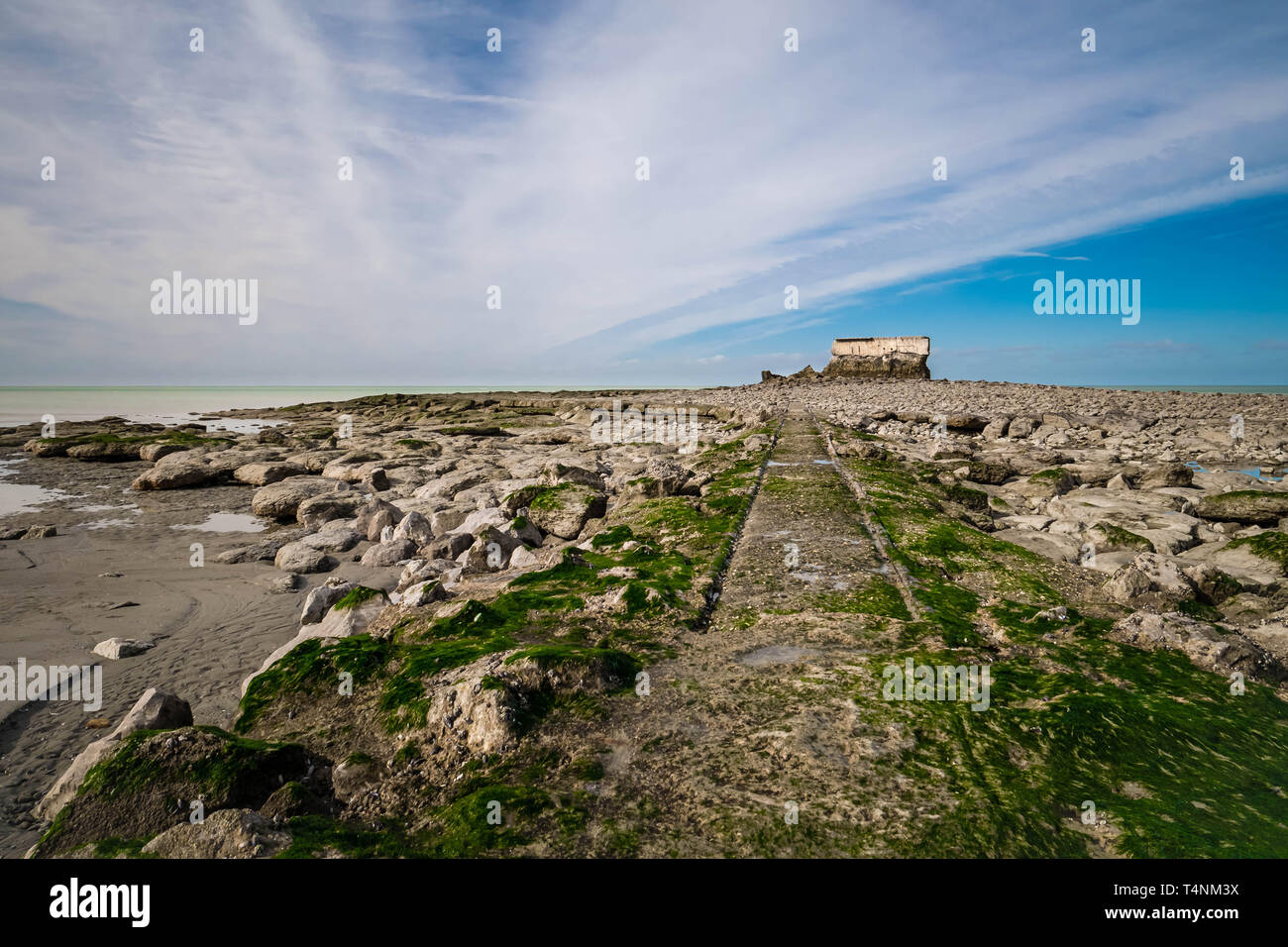 Abandoned railtracks leading through rocks to an ancient Fort on the coastline - Stock Image