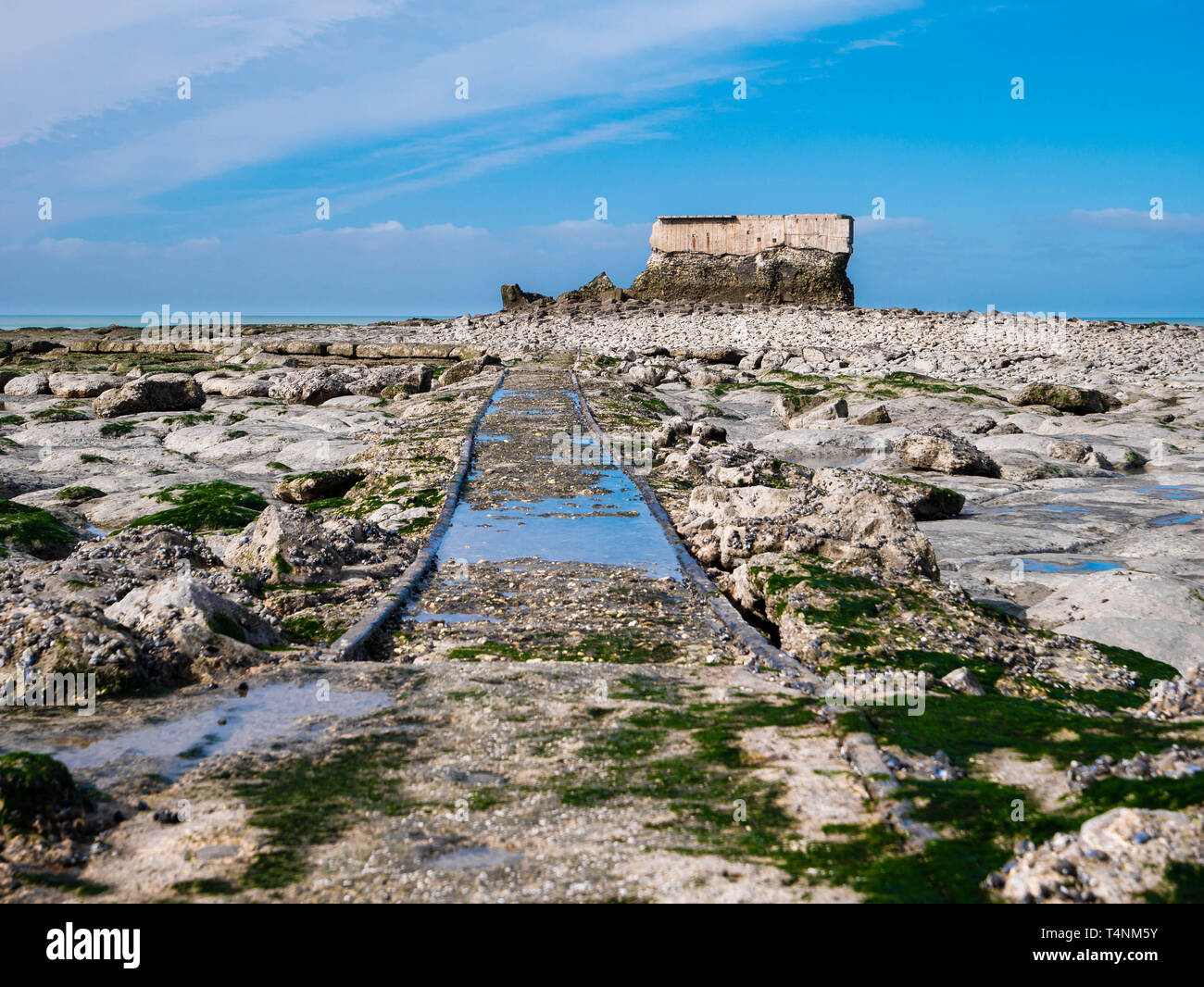 Ancient railtracks leading through rocks to an abandoned Fort on the coastline - Stock Image