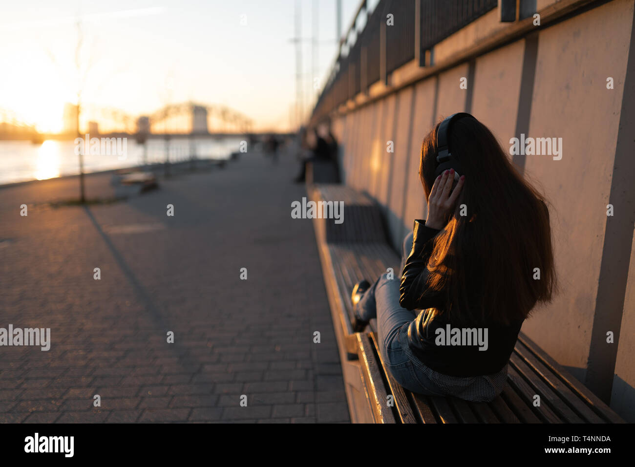 Young woman listens to music in closed headphones through her phone wearing a leather jacket and jeans at a sunset near river Daugava Stock Photo