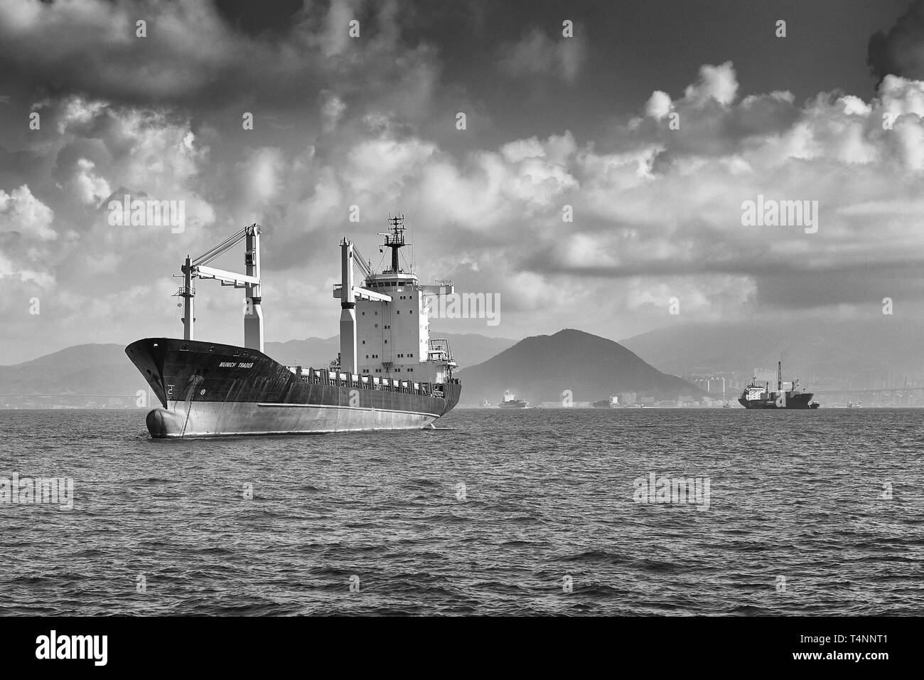 Black and White Photo Of The Cargo/Container Ship, MUNICH TRADER, In-Ballast And Anchored West Of Victoria Harbour, Hong Kong. - Stock Image