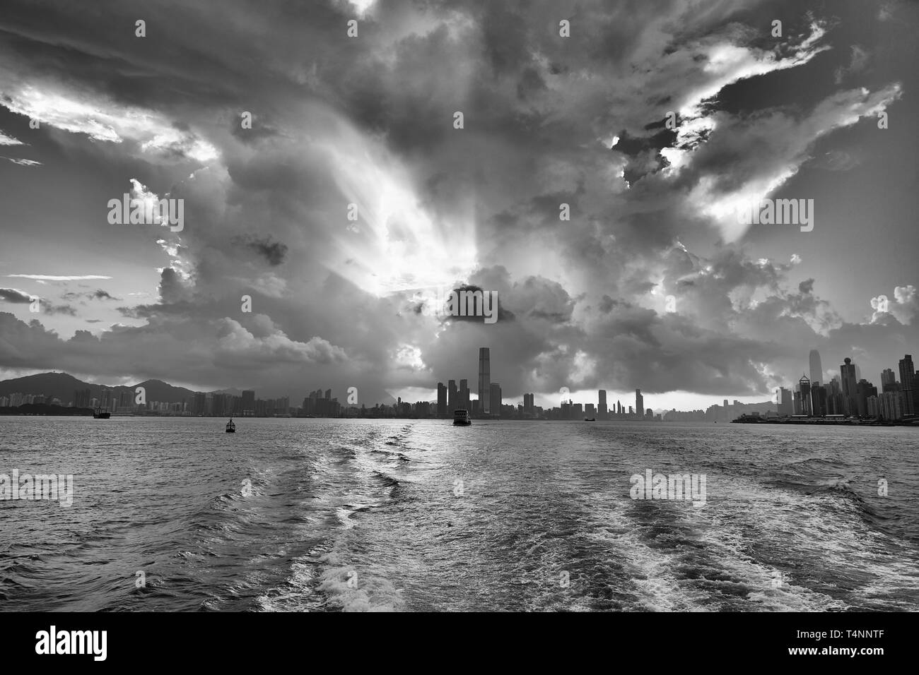 Black And White Photo Of A Giant Tropical Storm Cloud (Cumulonimbus), Illuminated By The Rising Sun, Over Victoria Harbour, Hong Kong. - Stock Image