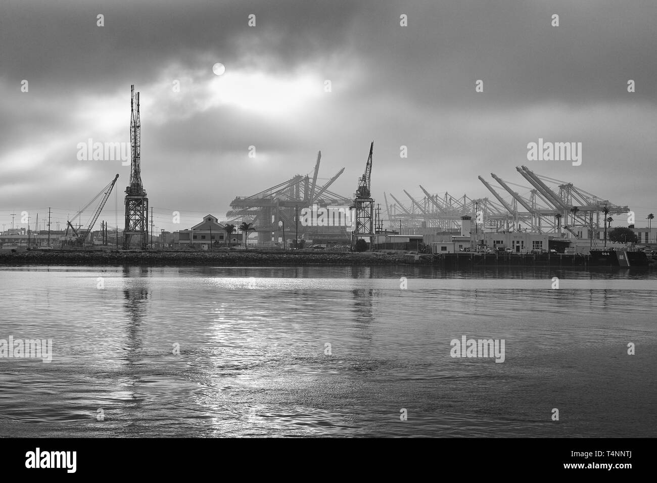 Black And White Photo Of The Sun Rising Over The Los Angeles Container Terminal And Terminal Island, California, USA. - Stock Image
