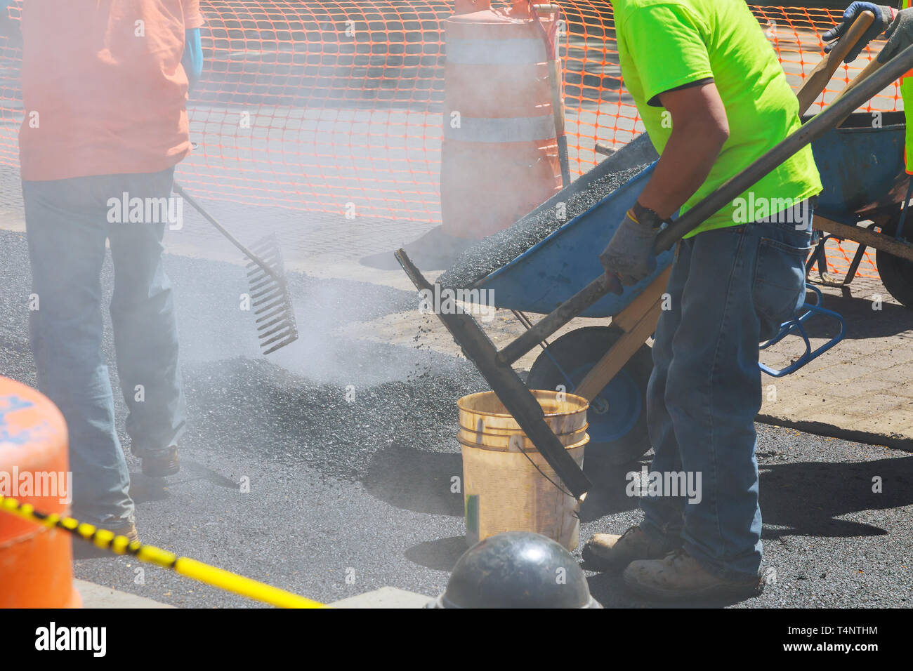 Workers on a industry aying fresh asphalt bitumen during