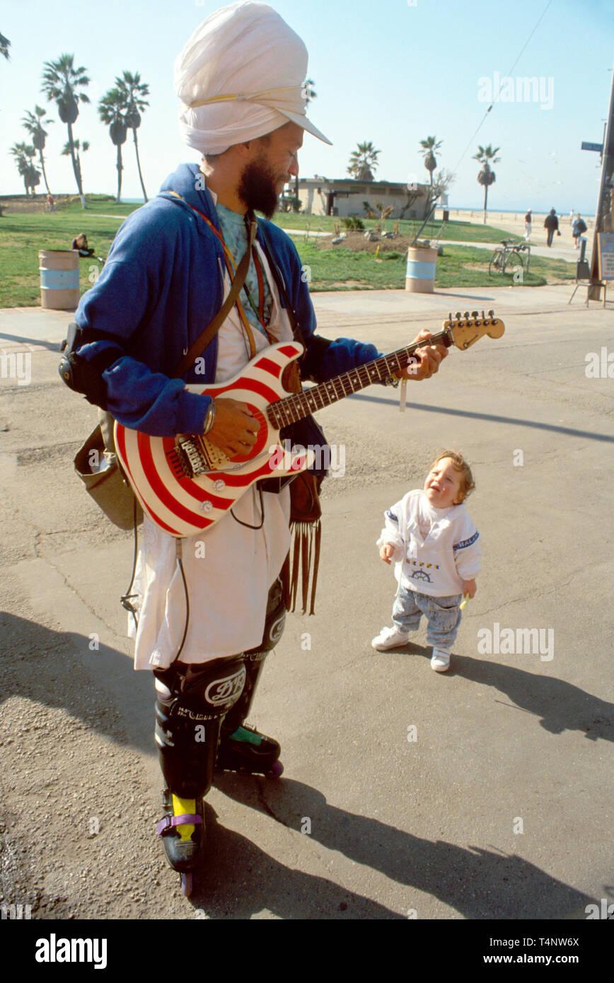 California Venice Beach swami street musician on rollerblades toddler - Stock Image