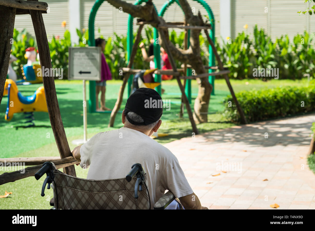 Old man sits on wheelchair looking at children playing on playground. Concept of youth recall, taking care of children. - Stock Image