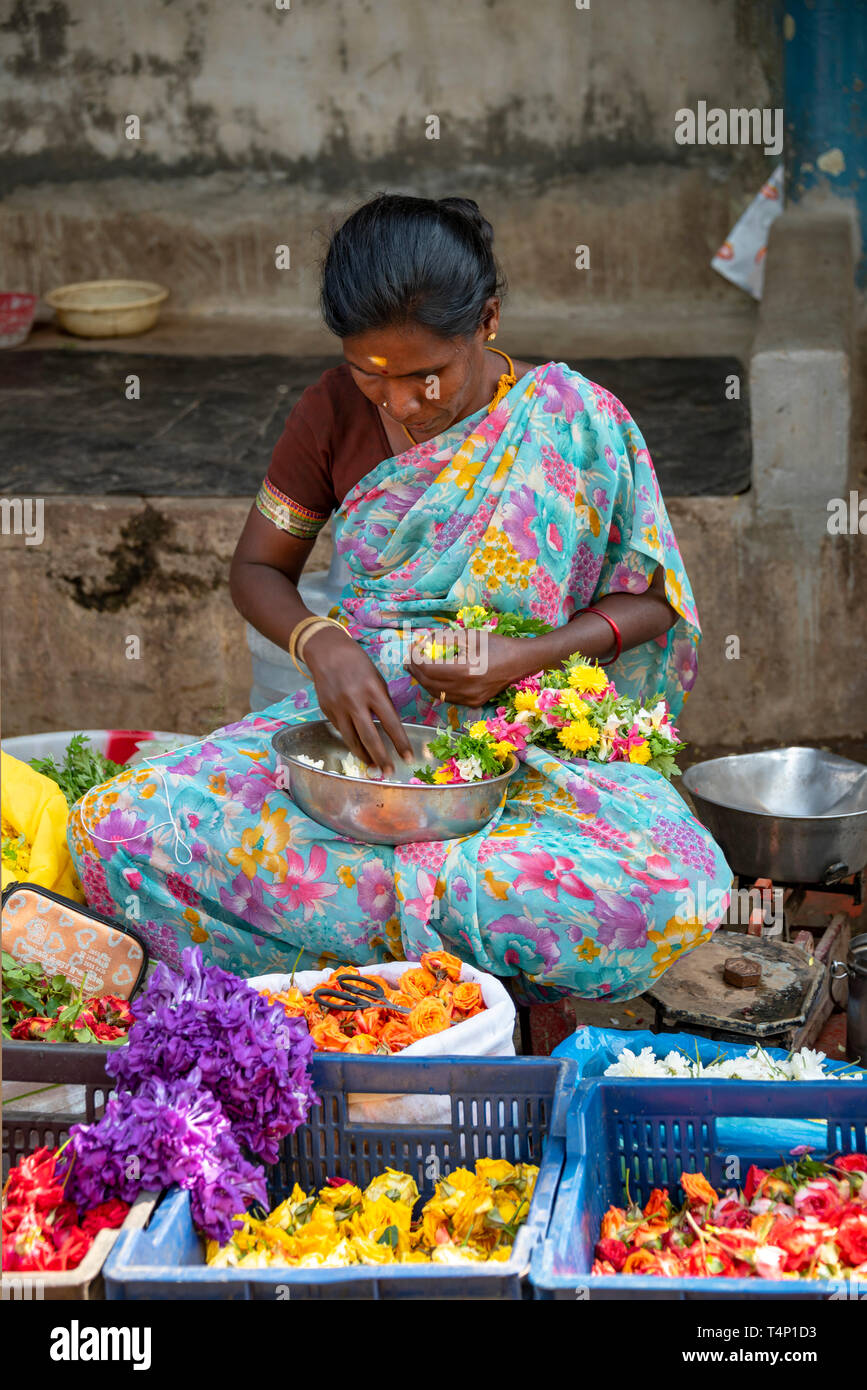 Vertical view of a lady hard at work making garlands at Mattuthavani flower market in Madurai, India. - Stock Image